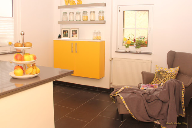 Küche mit Etagere von Depot, Porzelan und Edelstahl, IKEA Ohrensessel und Fußschemel